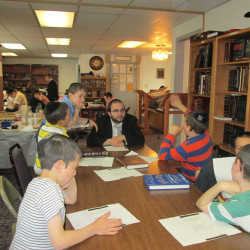 Kollel scholar Rabbi Yaakov Zions learning with boys at West Side Bais Medrash